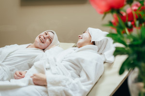 two ladies in robes laughing on group spa day