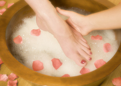 beautician giving relaxing pedicure with bubble foot bath