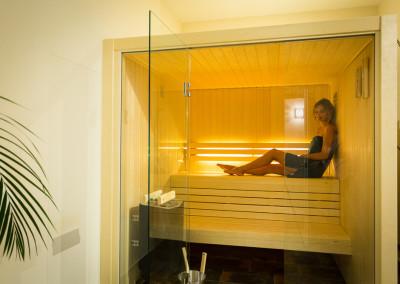 lady sat inside glass sauna room