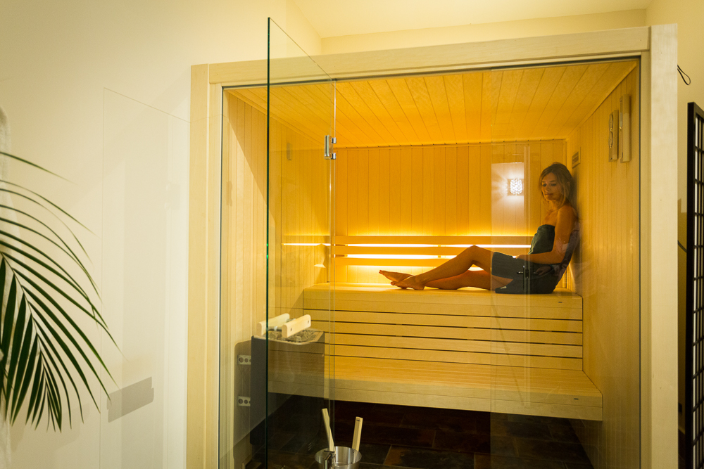 lady in a glass-fronted sauna on spa day