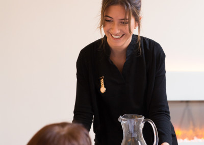 beautician serving jug of water to happy spa guest